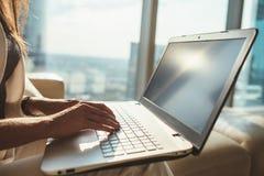 Primo piano del copywriter femminile che lavora al computer portatile che si siede nell'ufficio moderno Immagini Stock Libere da Diritti