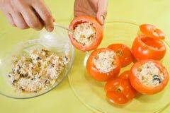 Primo piano del cuoco che farcisce l'insalata del pomodoro Immagine Stock