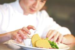 Primo piano del cuoco unico che aggiunge tocco finale sul suo piatto Fotografia Stock Libera da Diritti