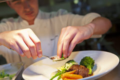 Primo piano del cuoco unico che aggiunge tocco finale sul suo piatto Fotografie Stock