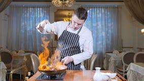 Primo piano del cuoco unico che cucina il piatto fiammeggiato di stile con le fette di fegato su una padella calda in ristorante  stock footage