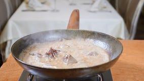 Primo piano del cuoco unico che cucina il piatto fiammeggiato di stile con le fette di fegato su una padella calda in ristorante  video d archivio