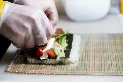 Primo piano del cuoco unico che prepara i sushi nella cucina, DOF basso Fotografie Stock Libere da Diritti