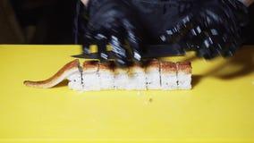 Primo piano del cuoco unico di sushi che prepara i rotoli europei con l'anguilla su un grande tavolo da cucina giallo Pagina trad stock footage