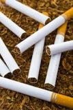 Primo piano del dettaglio delle sigarette sul fondo del tabacco Fotografia Stock Libera da Diritti