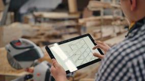 Primo piano del falegname che per mezzo della compressa sul lavoro che esamina progettazione della mobilia video d archivio