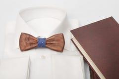 Primo piano del farfallino di legno sulla camicia classica bianca con il fondo marrone della luce del taccuino Fotografia Stock Libera da Diritti