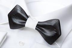 Primo piano del farfallino nero elegante di legno sulla camicia classica bianca Fondo di concetto di nozze e di affari Fotografia Stock Libera da Diritti