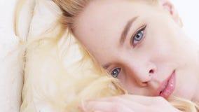 Primo piano del fronte della bella giovane donna con trucco perfetto, capelli biondi e gli occhi blu-e-grigi trovantesi su morbid archivi video