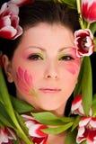 Primo piano del fronte della donna incorniciato con i tulipani Immagini Stock