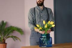 Primo piano del giardiniere appassionato che prende cura dei fiori gialli dentro fotografie stock