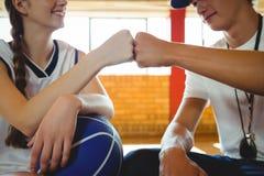 Primo piano del giocatore di pallacanestro femminile che fa l'urto del pugno con l'allenatore maschio Immagine Stock Libera da Diritti