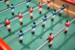 Primo piano del gioco di calcio di calcio-balilla sul piede verde del bambino del campo immagini stock libere da diritti