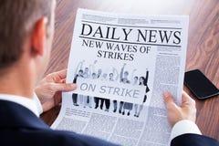 Primo piano del giornale di Reading News On dell'uomo d'affari fotografie stock