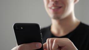 Primo piano del giovane sorridente che usando Smartphone, passando in rassegna in Internet o controllando le reti sociali su fond stock footage