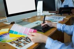 Primo piano del grafico femminile che per mezzo della tavola dei grafici allo scrittorio Fotografia Stock Libera da Diritti