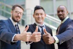 Primo piano del gruppo di affari che tiene i loro pollici su Immagine Stock