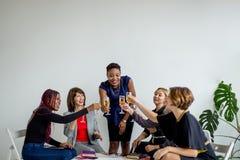 Primo piano del gruppo di persone di affari che tostano i vetri di champagne nell'ufficio fotografie stock