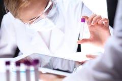 Primo piano del gruppo di ricerca scientifica con la chiara soluzione in laboratorio Immagine Stock