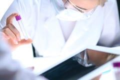 Primo piano del gruppo di ricerca scientifica con la chiara soluzione in laboratorio Il chimico femminile biondo tiene la provett Fotografie Stock