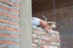 Primo piano del lavoro del muratore di processo della costruzione con l'installazione del mattone immagini stock libere da diritti