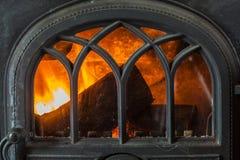 Primo piano del legno bruciante del fuoco in camino domestico fotografia stock