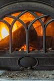 Primo piano del legno bruciante del fuoco in camino domestico immagini stock