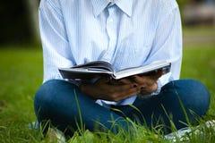 Primo piano del libro di lettura femminile su erba verde Immagine Stock Libera da Diritti