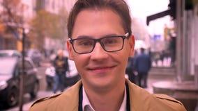 Primo piano del mA caucasico attraente che esamina diritto la macchina fotografica e che sorride felicemente Via urbana della cit video d archivio