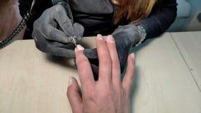 Primo piano del manicure che fa il manicure dell'hardware ad una ragazza metraggio di riserva della stazione termale nel †del s video d archivio