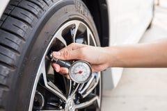 Primo piano del manometro della tenuta della mano per il pneumatico dell'automobile Immagini Stock Libere da Diritti