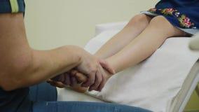 Primo piano del massaggio del piede del bambino nell'ufficio del massaggiatore archivi video