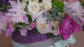 Primo piano del mazzo delle peonie variopinte e delle rose e del nastro blu sulla tavola bianca Nel negozio di fiori del fondo archivi video