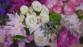 Primo piano del mazzo delle peonie variopinte e delle rose e del nastro blu sulla tavola bianca Nel negozio di fiori del fondo video d archivio