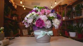Primo piano del mazzo delle peonie variopinte e delle rose e del nastro blu sulla tavola bianca Nel negozio di fiori del fondo Immagini Stock Libere da Diritti