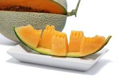 Primo piano del melone arancio affettato nei pezzi su un piatto bianco Immagini Stock