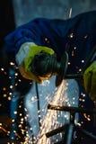 Primo piano del metallo di taglio del lavoratore con la smerigliatrice Scintilla mentre frantumano il ferro Fotografie Stock