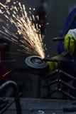 Primo piano del metallo di taglio del lavoratore con la smerigliatrice Scintilla mentre frantumano il ferro Immagine Stock Libera da Diritti