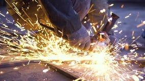 Primo piano del metallo di taglio del lavoratore con la smerigliatrice Scintilla mentre frantumano il ferro video d archivio