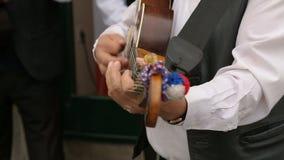 Primo piano del musicista maschio che gioca chitarra sulla via, prestazione di musica archivi video