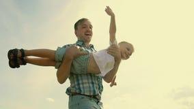 Primo piano del padre e del figlio che giocano insieme Il giovane padre gira suo figlio in mani video d archivio
