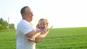 Primo piano del padre e di piccola ragazza felice sveglia che giocano insieme Il giovane padre gira sua figlia in mani Bambino stock footage