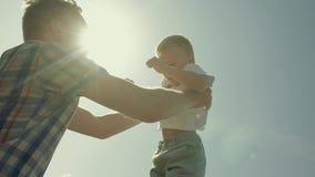 Primo piano del padre felice e del suo piccolo figlio Il padre lo getta su e prende archivi video
