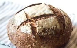 Primo piano del pane fresco e crostoso dell'artigiano del lievito naturale sull'asciugamano Immagini Stock Libere da Diritti