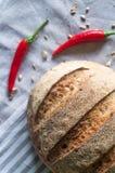 Primo piano del pane piccante dell'artigiano e di due peperoni roventi su kitc Immagini Stock