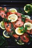 Primo piano del pesce rosso affettato con le fette di limone e di aneto Un piatto delizioso è preparato immagine stock libera da diritti