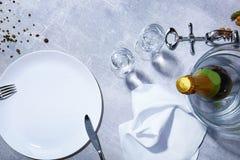 Primo piano del piatto bianco, forcella, coltello, bottiglia verde di champagne, vetri, condimenti su un fondo grigio Fotografia Stock