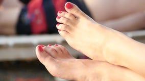 Primo piano del piede della donna sulla spiaggia La ragazza mostra le sue dita, unghie ha dipinto con lacca rossa video d archivio