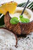 Primo piano del pinacolada in noce di cocco sulla spiaggia Immagine Stock