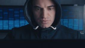 Primo piano del pirata informatico maschio pericoloso nel funzionamento del cappuccio su un computer nel centro dati Concetto di  stock footage